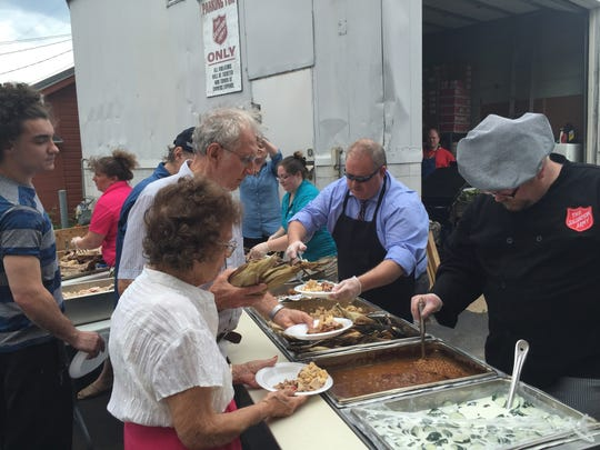Mayor Robert Mielke (center) serves food to those waiting in line at the Salvation Army pig roast Wednesday.