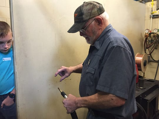 A torch used to weld metal is shown by welding instructor Bill McCleese. McCleese was teaching students from the county through a skilled trade camp at Terra State Community College this week.