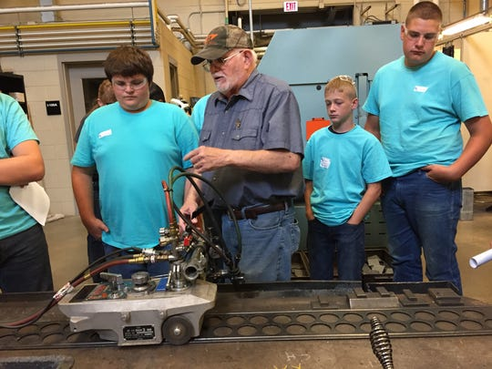 During a skilled trade camp, welding instructor Bill McCleese shows students a cutting machine at Terra State Community College.