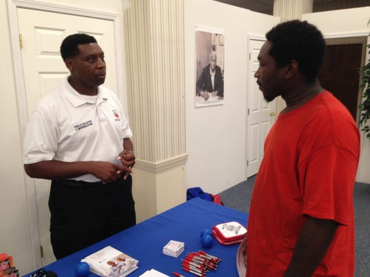 Errick Merriweather, public educator with the Jackson Fire Department, discusses employment with Gregory Ware, during a job fair at the Jackson-Madison County NAACP branch on Thursday.