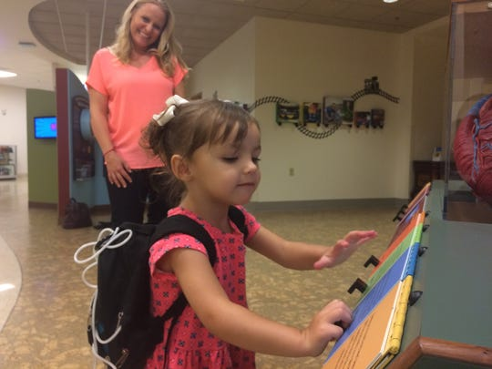"Laurie Shook smiles as her 3-year-old daughter, Addie, plays with a game that allows her to listen to different animals' heartbeats at Cardon Children's Medical Center in Mesa. Laurie said Cardon is Addie's ""safe place,"" to feel like she's ""normal."""