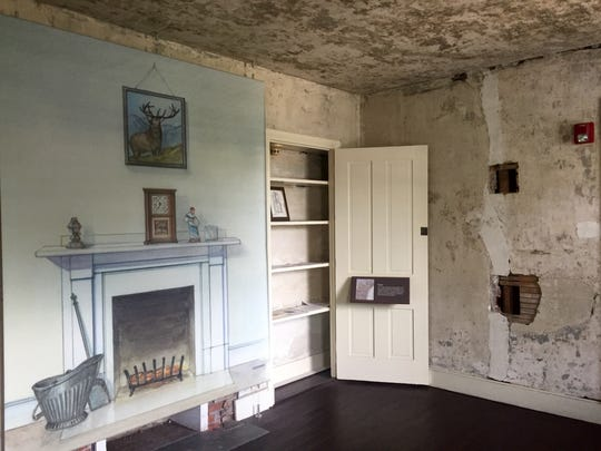 The interior of the Edgar Allan Poe house is empty save for illustrations and information.