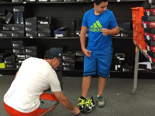 Bob Hix, left, checks the fit on a pair of new cleats for son, Collin, during going-out-of-business sales at Sports Authority, 425 S. College Ave. The store plans to close Monday.