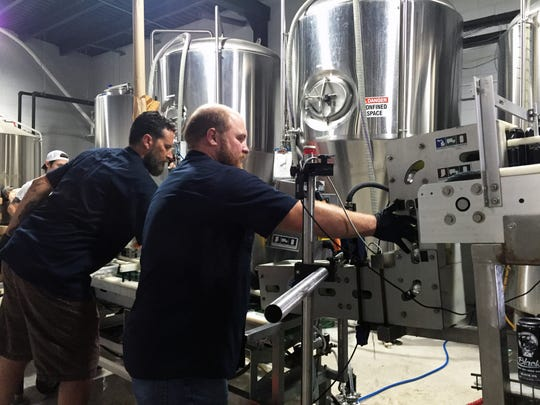 Tom Streit (right), lead operator and technician with Indiana Mobile Canning, helps run their mobile canning line at Black Acre Brewing.