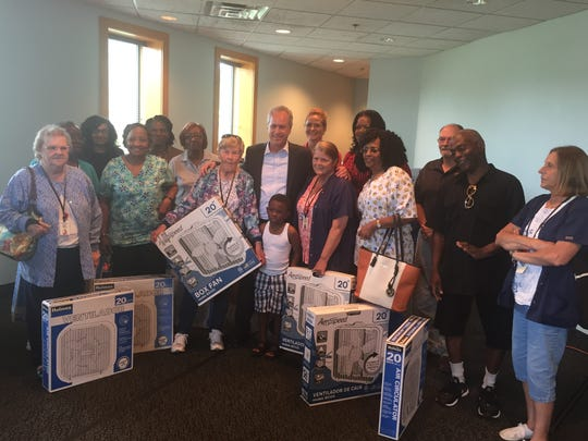 Louisville Mayor Greg Fischer poses with a group of people who received free fans at the Bridge of Hope Neighborhood Place on Wednesday.