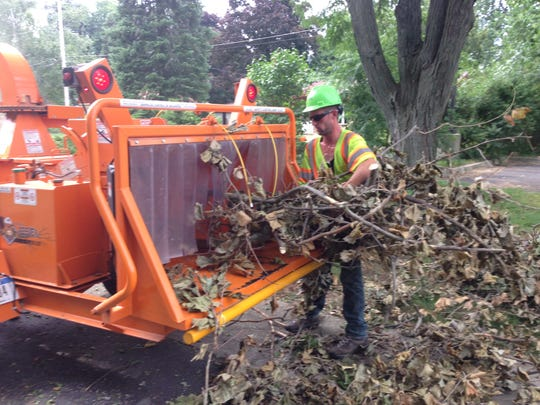 Chris Fraser of Asplundh Tree Expert Co. puts fallen tree limbs in to a chipper Thursday in Haslett.