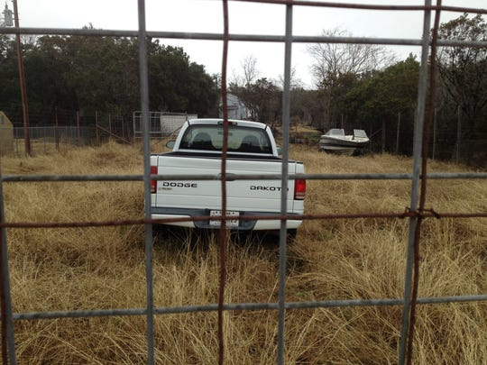 Felix Vail's pickup behind a tall fence on property in Canyon Lake, Texas.