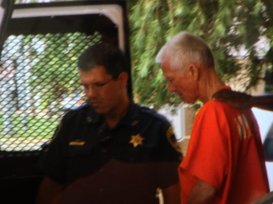 Felix Vail, dressed in an orange jumpsuit, is loaded into a Calcasieu Parish sheriff's bus.