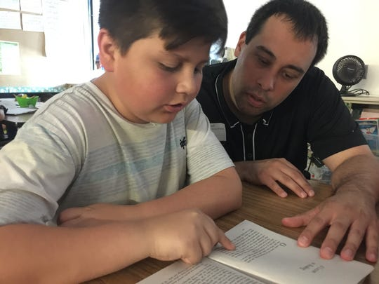 Mentor Brian Joy helps Steven, 11, become a better reader. Steven used to express frustrations about his home life and struggles with learning by leaving class; now, he has better coping skills.