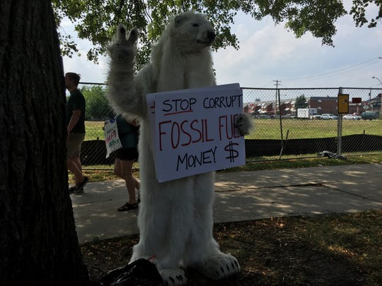 A man dressed in a polar bear outfit protests climate change policy outside the Wells Fargo Center.