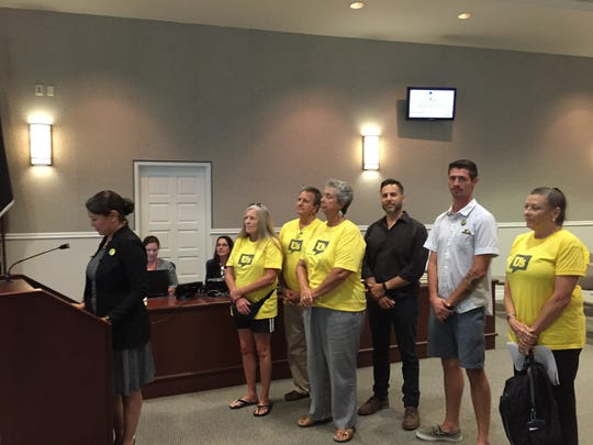 Melissa Martin speaks before Cocoa City Council with supporters standing with her.
