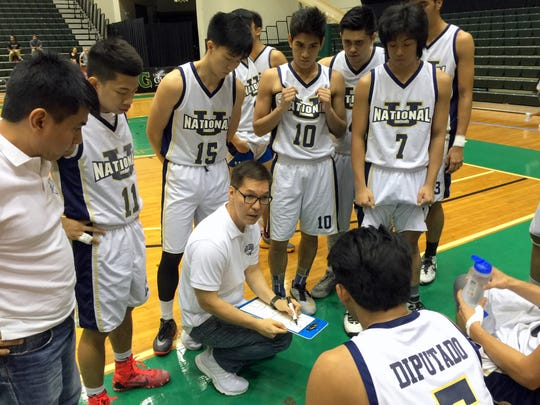 National University players surround their coach during a timeout of their game against Team Guam in the Guam Invitational Basketball Tournament Tuesday at the University of Guam Calvo Field House.