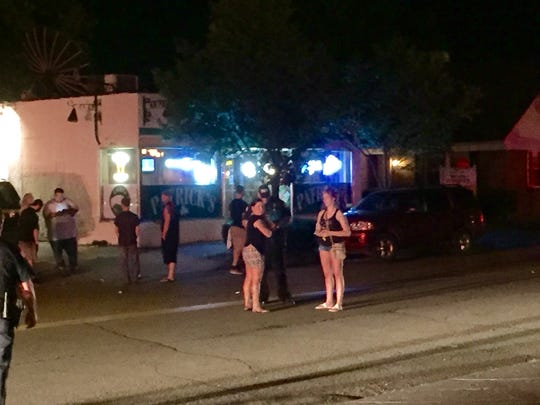 Police talk with people outside Patrick's bar on College Avenue following a reported shooting there early Thursday.