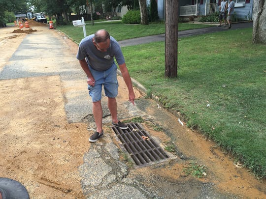 Millville resident Russell Knoll on Friday points out underground pipes that are supposed to deal with stormwater on Peach Drive. The grated covering, and pipes, are just off the curb of his house.