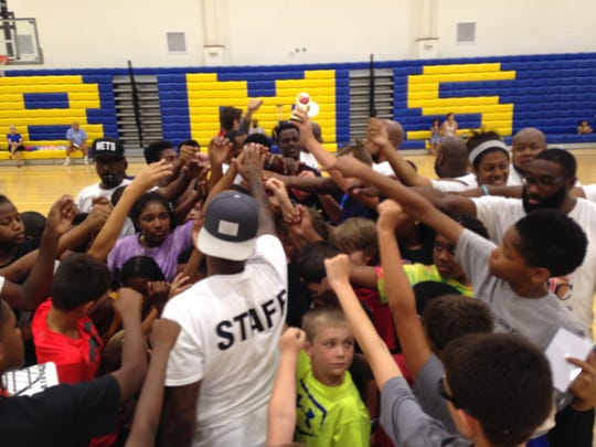 Andre Collins (center, white shirt) breaks out the campers on the final day of his camp.