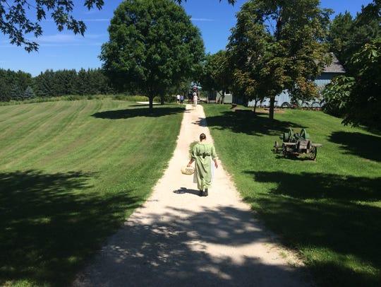 A volunteer at Pinecrest Village walks along a path