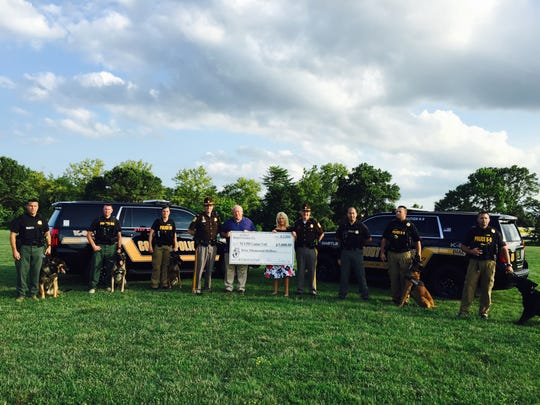 Michael and Donna Freebery present the New Castle County Police K-9 Unit with a $5,000 donation.