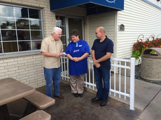 Tammy Provisor receives a check for $500 from Jerry Meador with Monogram Foods, left, in front of Culver's in Stevens Point as store owner Russ Trzebiatowski looks on. The funds will go towards Provisor's trip to see her son Ben wrestle in the Rio Olympic Summer Games.