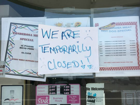 A sign is seen on the window of Ponderosa Meat Co.