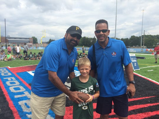 """Brett Rybarczyk, 8, of Cleveland, poses with Hall of Fame players Franco Harris (left) and Andre Reed (right) during the Pro Football Hall of Fame's """"First Play"""" event in Canton, Ohio."""