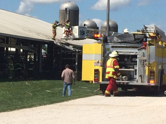 Members of the Manitowoc Fire Department use their laddar truck to survey the barn fire. The yellow truck is part of the Rockwood Fire Dept.