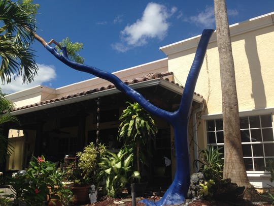 A dying tree in the courtyard at La Corte Courtyard Garden Bistro in Cape Coral is painted blue as part of a piece of artwork during renovations.