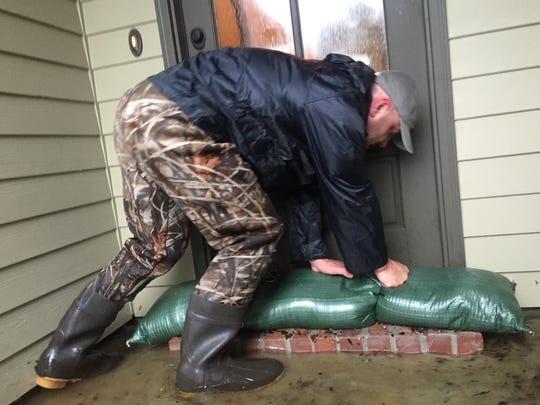 David Schendel, a Sawgrass Subdivision resident, stacks sandbags outside his front door Friday.