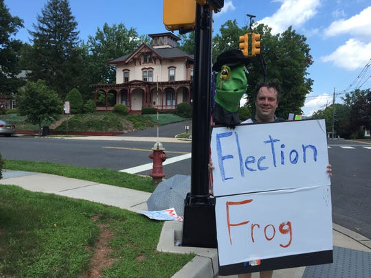 "A protester outside of Edison Research on Saturday holding a frog head puppet and sign, playing on the words ""election fraud."""