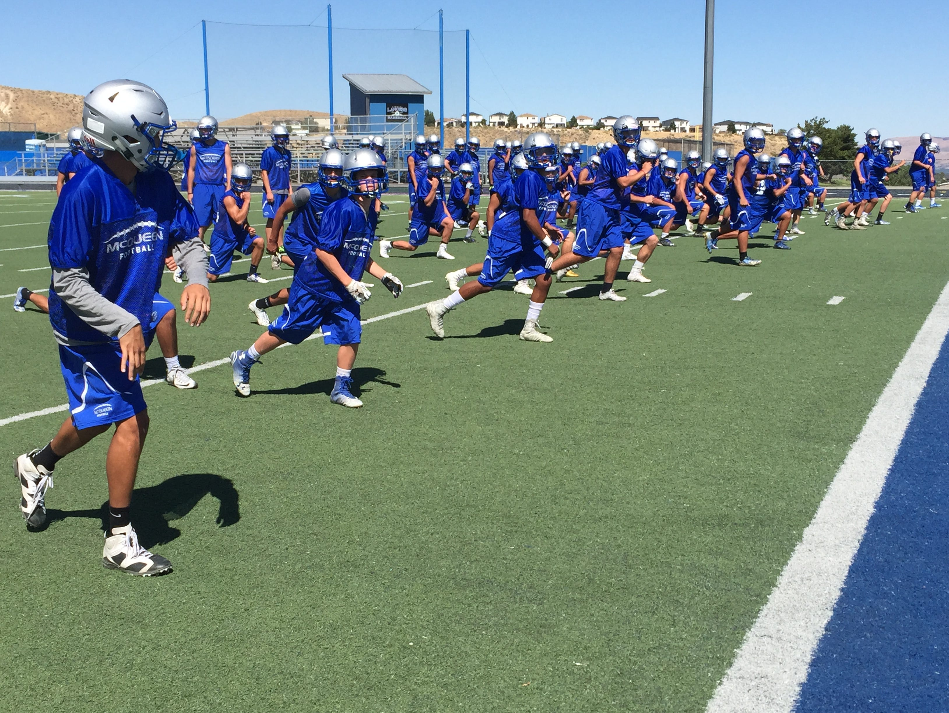 The McQueen football team warms up last week at the school.