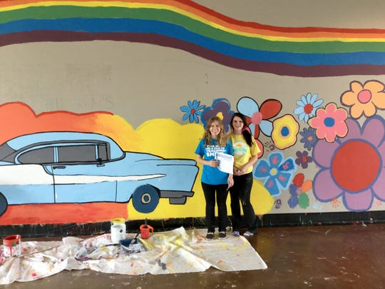 Childtime camp teacher, Hollie Hulst (Left) was the supervising artist drawing a colorful, whimsical, streetscape mural on the inside wall of the old Firestone building in Royal Oak. 35 children campers at Childtime helped paint the mural. Friend Quincie (right)stands with Hollie in front of the mural.