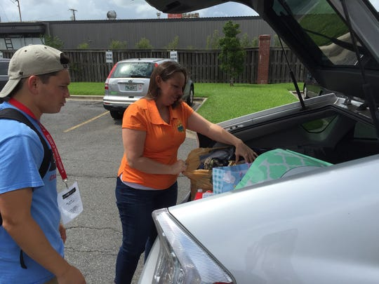 Osh Leveque-Perkins drops off items she collected for flood victims Tuesday afternoon at The Daily Advertiser.