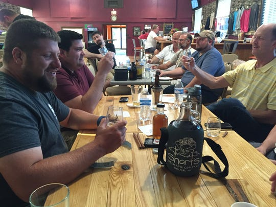 Andrew Rademacher, left, vice president of Red Ledge Brewers, tastes a citra pale ale he made for a recent club meeting,