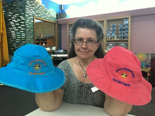 CAPPED Executive Director Tresa VanWinkle holds the hats they give out to local children in their Sun Safe Program. CAPPED's goal is to reach $16,000 to buy more hats for the program.