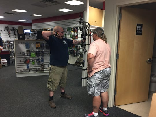 Gwen Cole, right, of Insight Archery, helps Andrew Patterson adjust his compound bow.