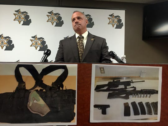 Macomb County Sheriff Anthony Wickersham displays photos of weapons seized from a murder suspect's car after a police chase, during a press conference on Wedneday, Aug. 17, 2016. Christina Hall, Detroit Free Press