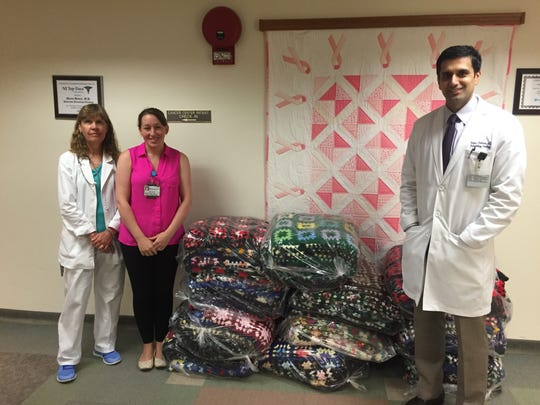 Diane April-Cooper, medical technologist; Jennifer Exley of the marketing department and Dr. Waqas Rehman, MD, accepted 90 granny-square afghans for the chemo therapy unit at Hunterdon Medical Center from an anonymous donor and Home News Tribune reader.