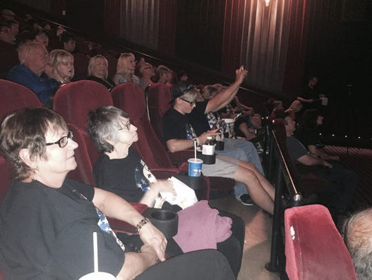 Members of the Post family look on at a viewing party