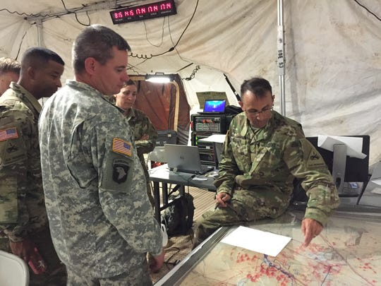Soldiers with 1st Armored Division Sustainment Brigade go through a briefing during the command-post exercise known as Iron Forge.