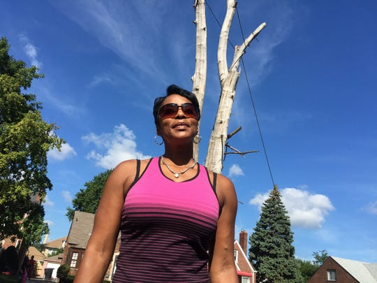 East side Detroiter Oriana Williams stands near a dead tree in her front yard on Thursday, Aug. 18, 2016, as a crew was cutting it down, much to her relief. The ash tree had been dead for four years.