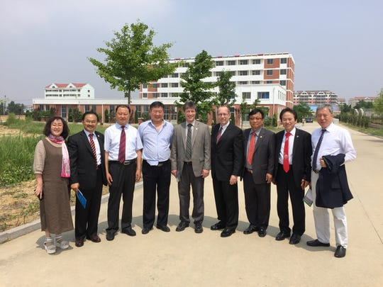 City officials stand with educators from South Korea and China in front of student dormitories and a preparatory school. In the middle is Assistant City Manager for Community and Economic Development Ted Dearing, and to his left is Mayor Dave Walters.
