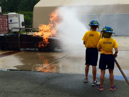 Alex Chin and Sephanie Alessio battle a fire at the Morris County Cadets render aid to during a drill at the Morris County Public Safety Youth Academy.