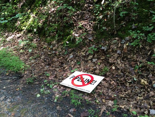 A pipeline opposition sign lies on the ground near