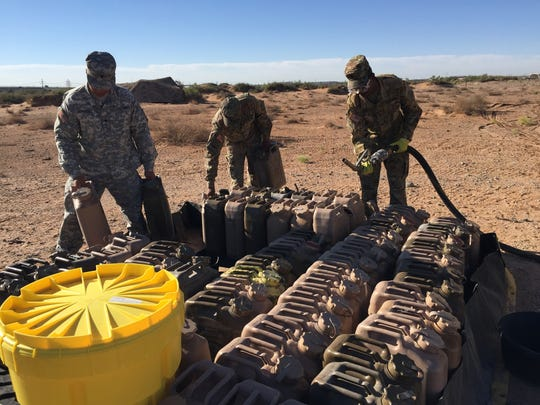Soldiers with 1st Armored Division Sustainment Brigade fill up gas cans with fuel to power generators during the Iron Forge exercise.