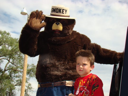 Smokey Bear waves to the crowd in the parade in Carrizozo