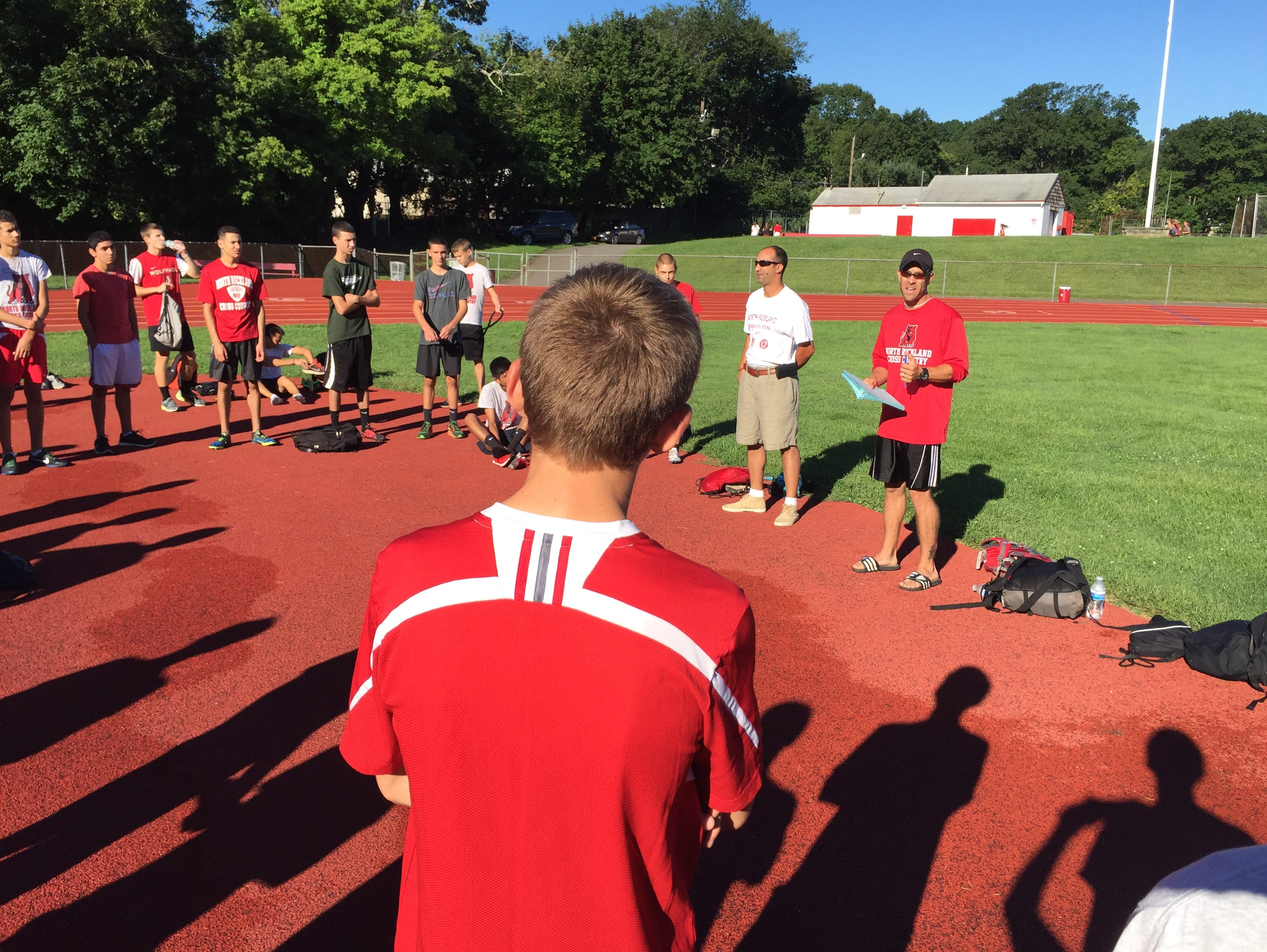New North Rockland varsity boys cross-country coach Chris Lent (r) speaks to team Monday.