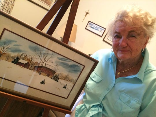 100-year-old Evelyn Reddin Fodden stands with one of her water color paintings.