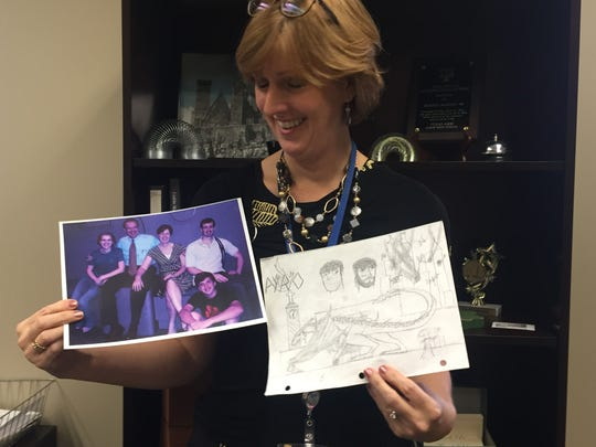 Bonnie Martin, mother of award winning playwright Cameron Martin, poses with a current family portrait (left) and a drawing of a dinosaur by her teenage son (right)