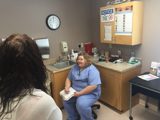 Nurse practitioner Casey Brooks talks with a patient