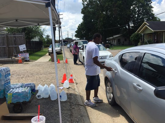 Cars line Coolidge Street Wednesday as volunteers accept and distribute donations at an independent center started by Shannon Cooper and other members of a Facebook group that connects Acadiana flood victims with resources.