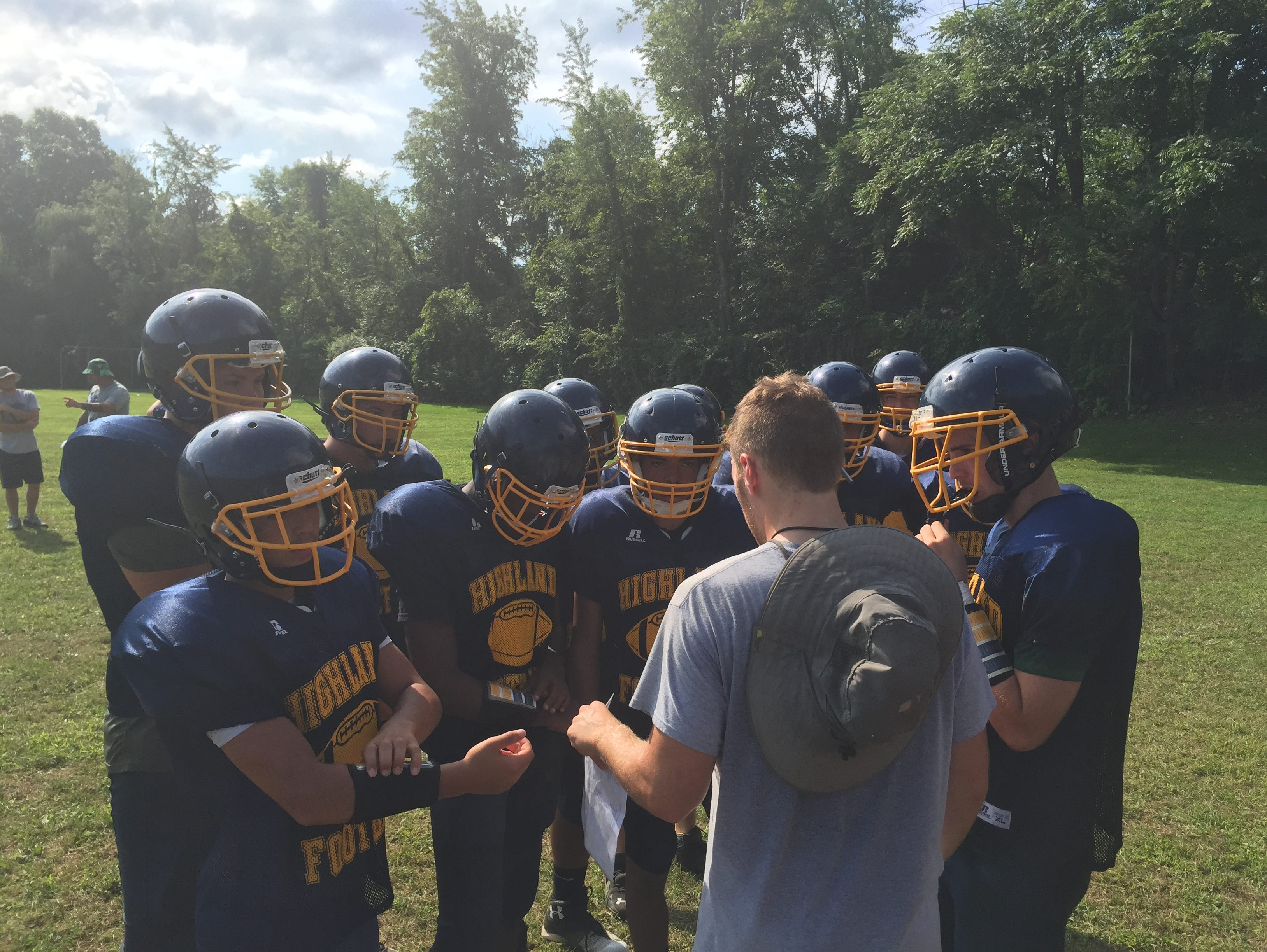 Members of the Highland High School football team huddle with offensive coordinator Tom Truscello.